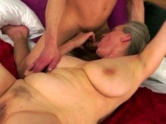A granny with saggy tits is getting penetrated on the bed