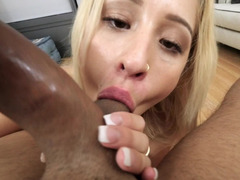 A blonde is receiving some cum in her mouth from a black dick