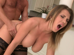 A blonde with large tits is getting her hands around a big cock
