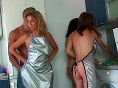 Three women are showing off their bodies to a man in the kitchen