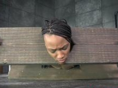 Tied ebony sub in pillory gets spanked