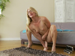 A small tits blonde is sitting down on a dildo that is long and firm