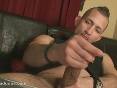 A hunk takes his prick out of his pants to play with it