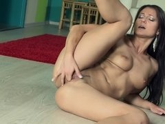 A young slut is on her ass on the floor, massaging her pussy lips