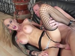 Tattooed honey is getting her big fake tits fucked on the sofa
