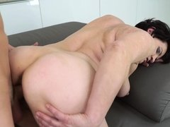 A granny is sucking a young cock on the sofa close to the camera