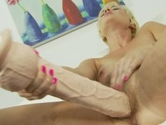 A blonde that likes her toys is using a giant dildo on her pussy