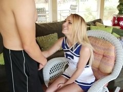 A blonde cheerleader is showing her charms on the couch