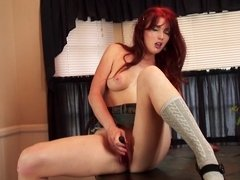 Redhead rams a large dildo into her wet and sexy pussy here