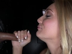 Blonde with long hair uses her mouth in a glory hole on a sausage