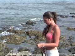 A brunette is naked at the beach, masturbating and sucking dick