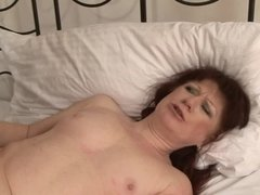 A redhead milf with small tits is getting a large black cock