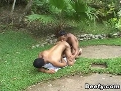 Two black studs make doggy style gay love in a forest