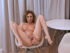 Petite MILF Dafna May masturbates on a chair