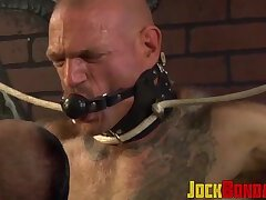 Hunk in bondage gear enjoying domination by his buff partner