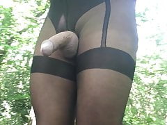 Black Crotchless suspender tights in the woods.