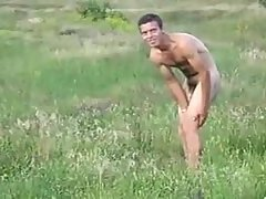 Nude guy playing in the field