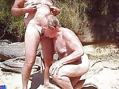 Old man sucks another man's penis on a beach