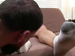Bald hunk has his feet worshiped while stroking his cock